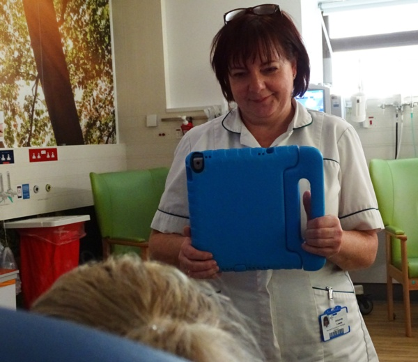 Occupational therapist uses iPad to film mum and baby