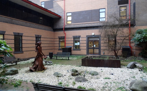 The garden courtyard near Morriston Hospital's Powys Ward. A metal sculpture of a woman stands on a white gravel area near a raised wooden flower bed.