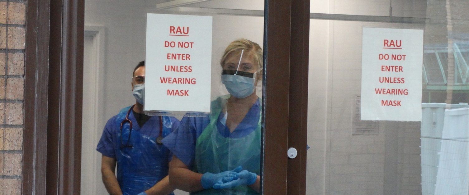 Image shows two clinical staff in face masks and face shields looking out