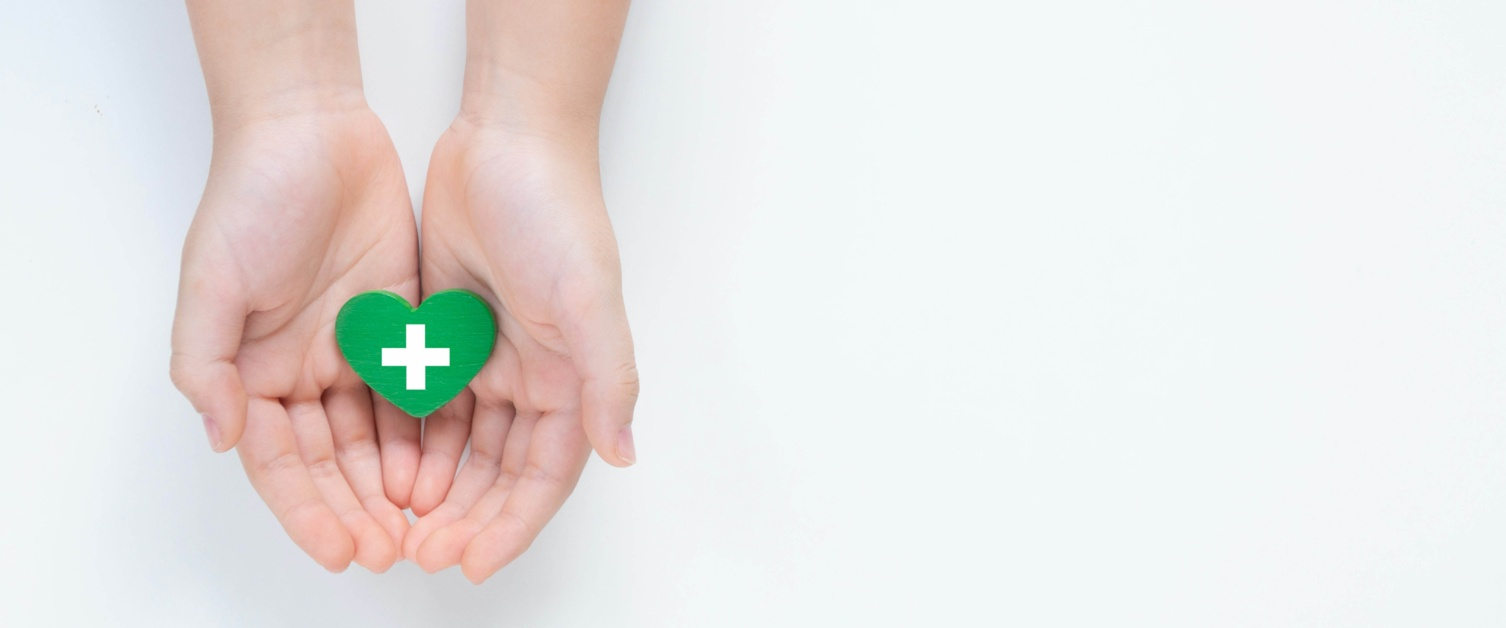 Image shows hands and wrists. Open hands hold a green heart.