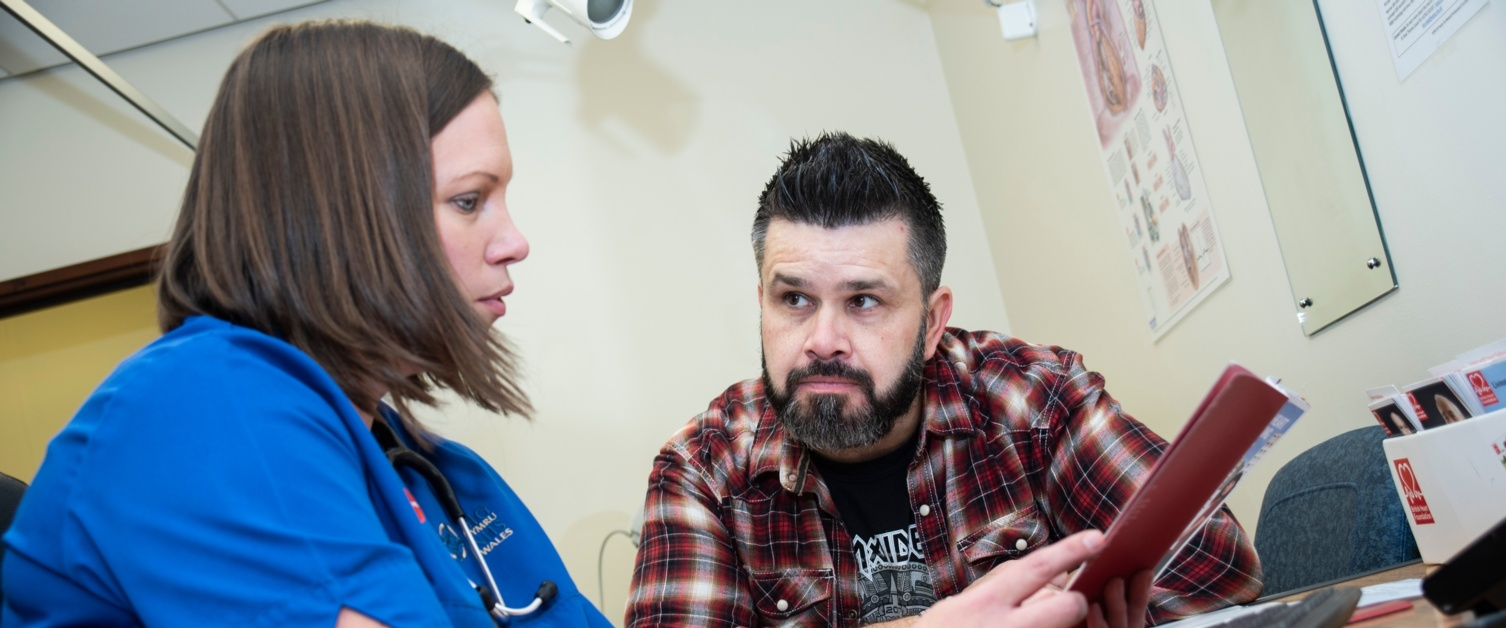 A female nurse on the left talks to a male patient on the right about his condition