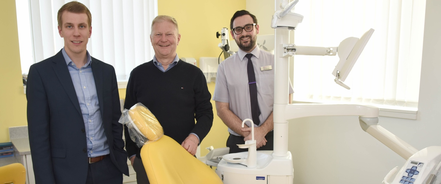 Three dental practice employees standing next to dental examination chair