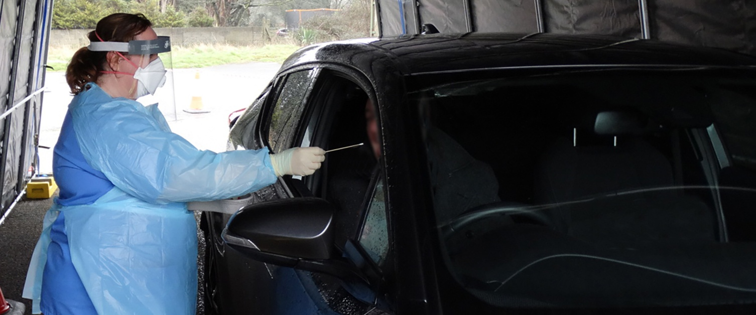 A nurse in protective clothing swabs mouth of a man in a car at testing unit
