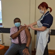 CEO of the CAE Franck Banza is pictured receiving an injection of COVID-19 vaccine from GP practice nurse Heather Featon.