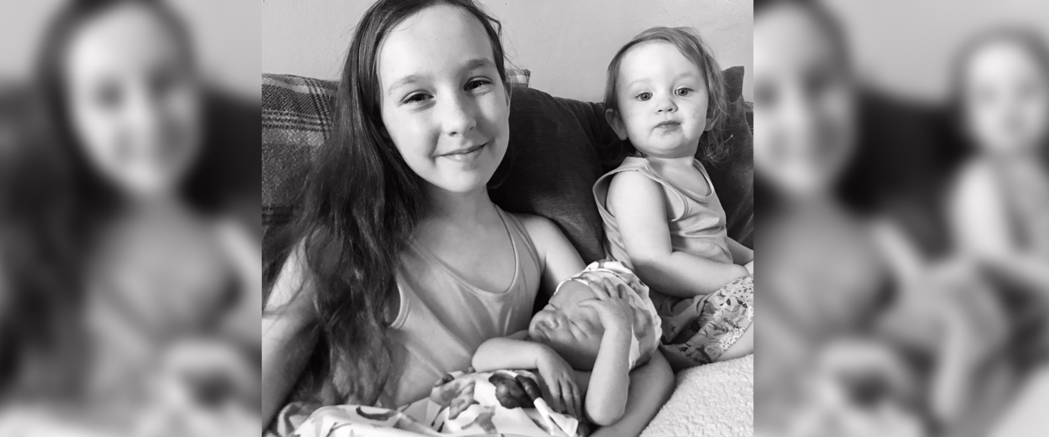 Two little girls, one of them holding a baby
