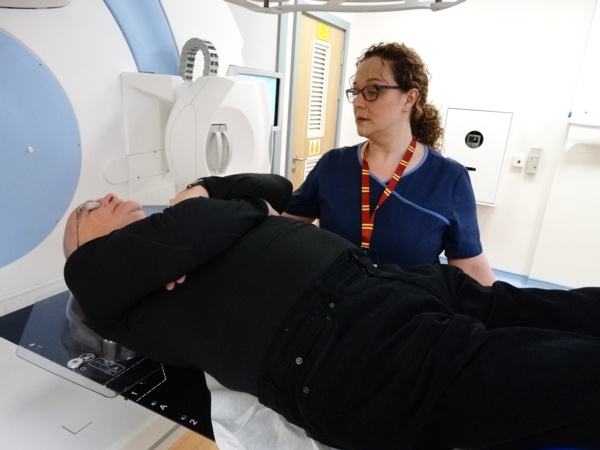 A man lying on his back new to radiographer and radiotherapy machine