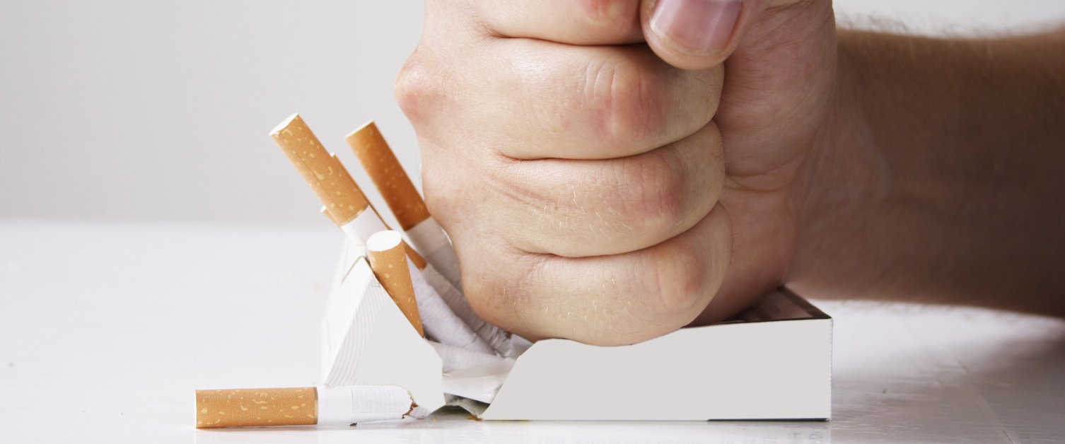 Picture shows a clenched fist crushing a packet of cigarettes.