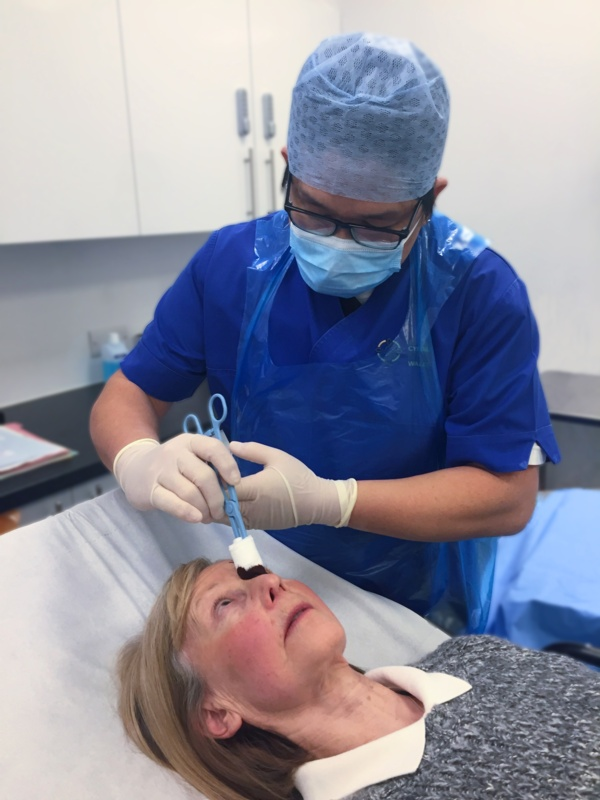 Nurse carries out eye procedure on patient