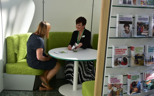 Two women talk at a table in a Macmillan Information Pod