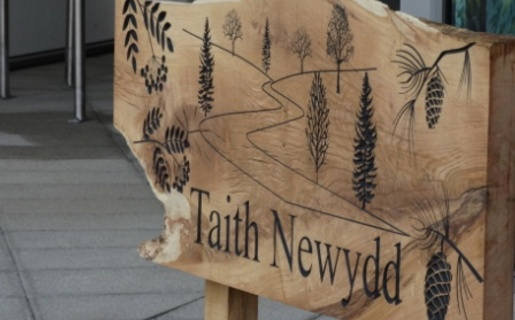A wooden sign outside Taith Newydd.