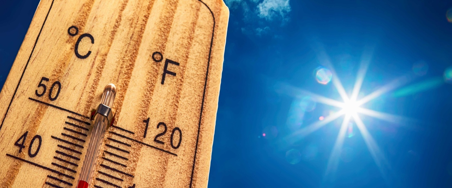 Image of thermometer up close showing high temperature and blue sky.