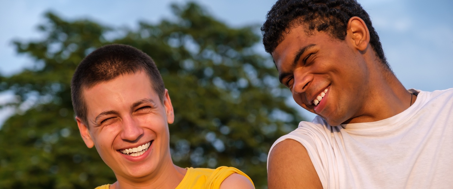 Two young men smile at each other while showing off the plasters on their arms after vaccination.