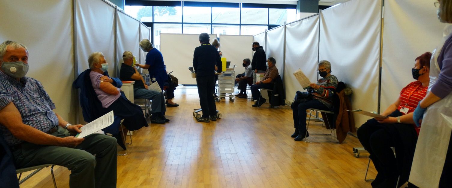 Image shows 10 people sat on chairs in a room.