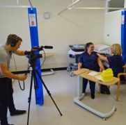 A photo of a nurse receiving her flu vaccination while being on film