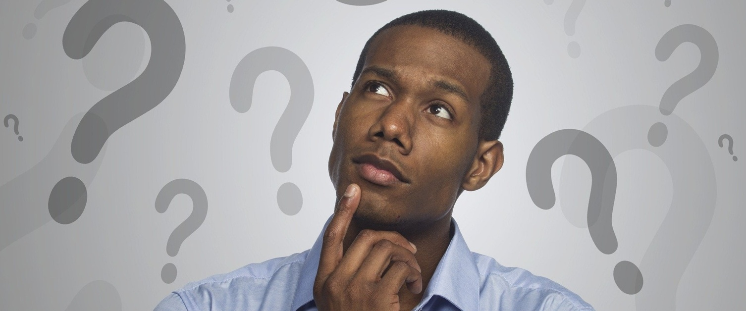 A man with his hand under his chin looks up at lots of question marks around him.