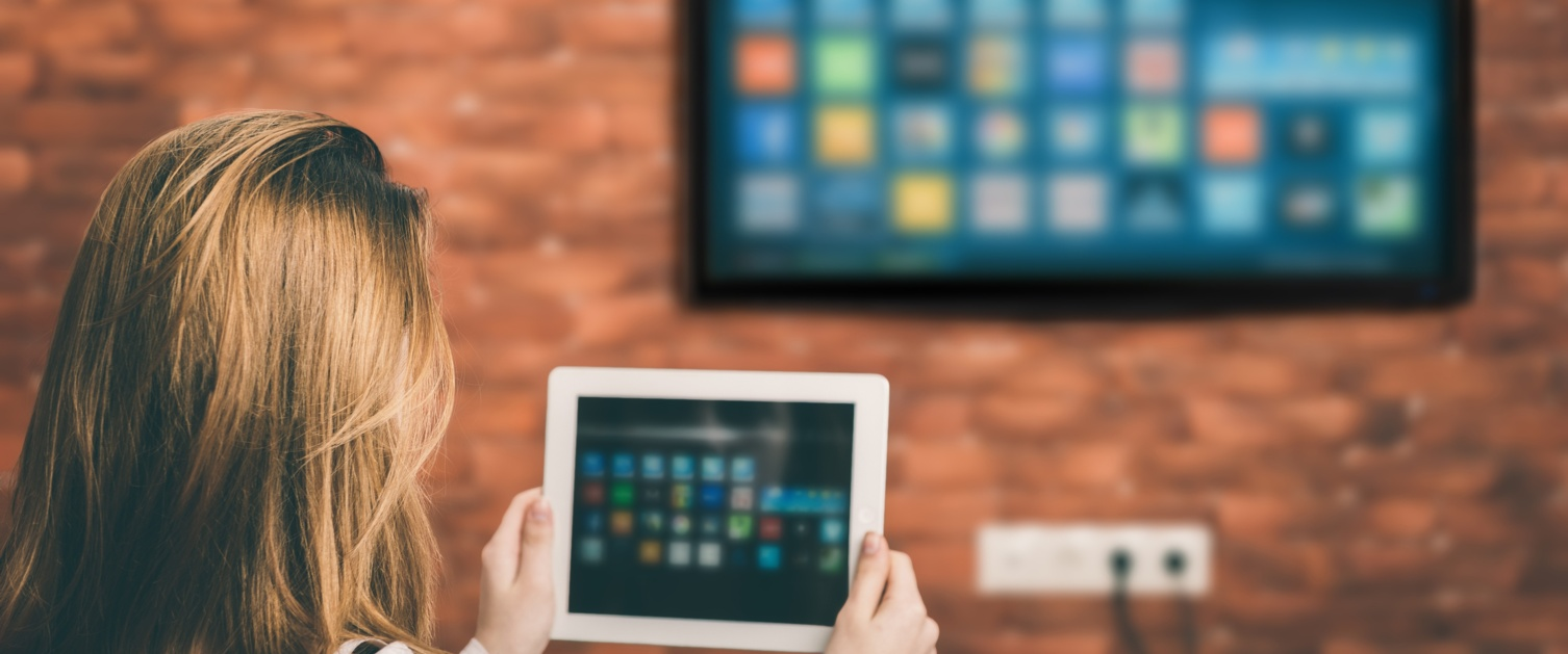 A woman looks at a tablet computer and a TV is on the wall