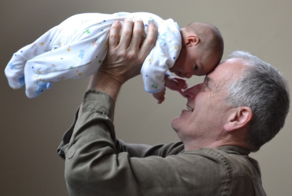 A grandfather holds a baby aloft with both hands. Their foreheads touch