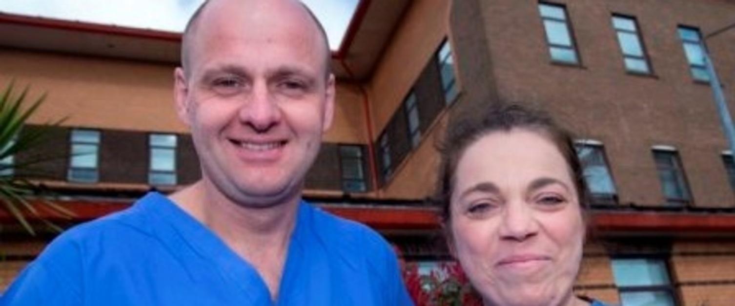 A man and a women,  David Johnston and Dominique Potokar, smiling at the camera outside Morriston Burns Centre.