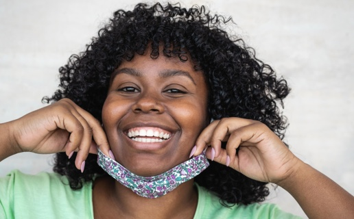 Close up of smiling woman who has pulled COVID face mask down to her chin.