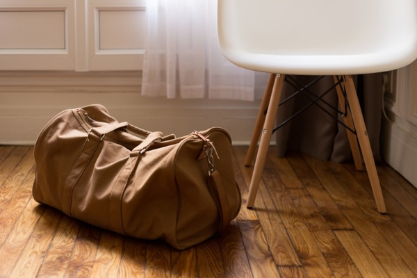 A brown bag placed on the wooden floor next to a white chair.