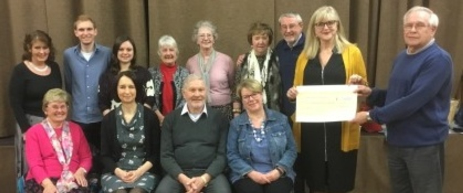 The congregation of a Swansea church presents a cheque to the staff of Ty Grangoch