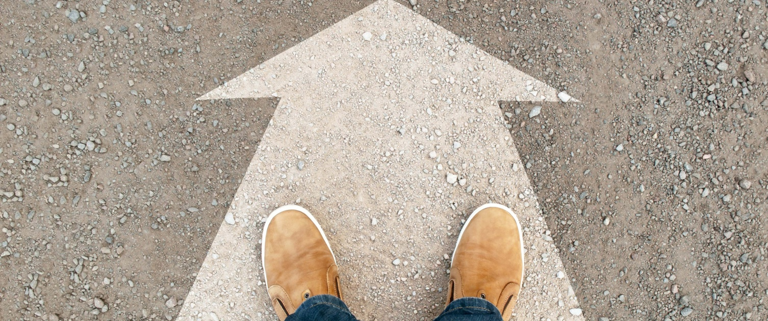 Image shows feet stood on large arrow painted on ground.