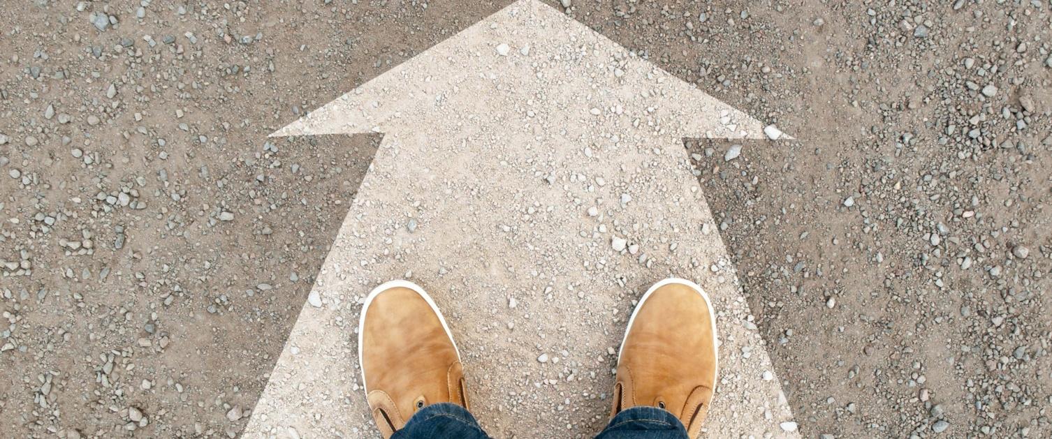 Image shows feet stood on large arrow painted on ground.