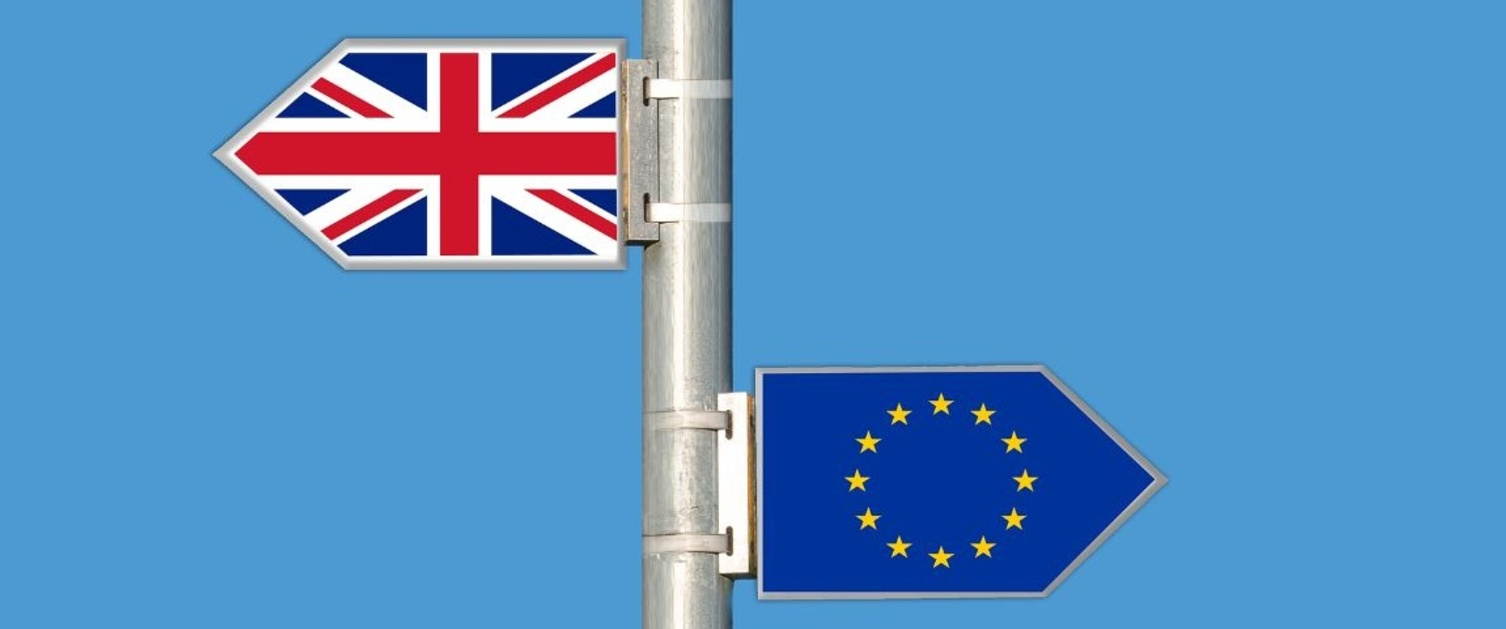 A sign with a Union Jack Flag and European Flag facing opposite directions.