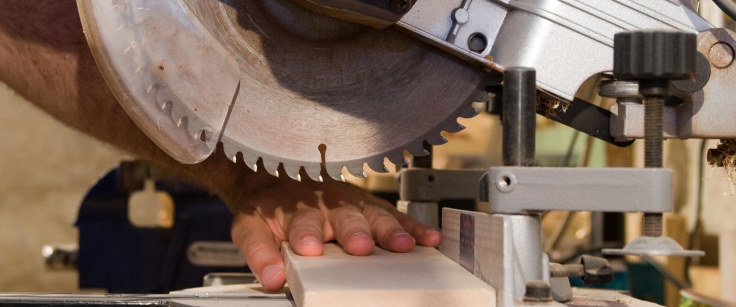Image shows close up of fingers by circular saw blade
