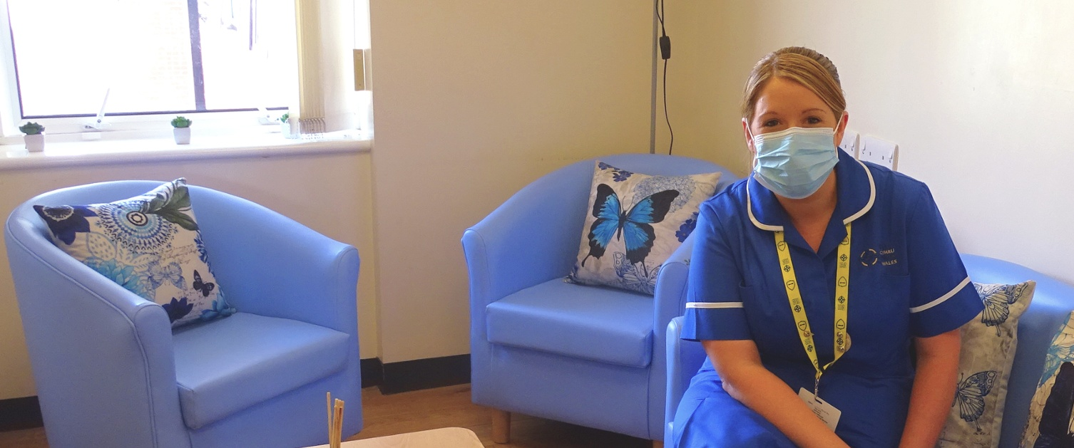 Picture shows a midwife sitting on a blue sofa in hospital quiet room.