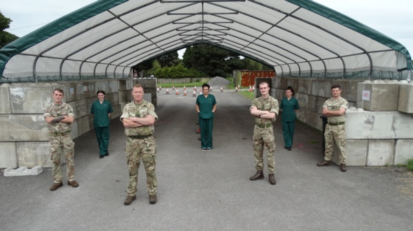 Four soliders are pictured standing socially distanced with three health care support workers.