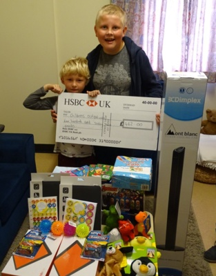 Ellis and Evan hand over the cheque