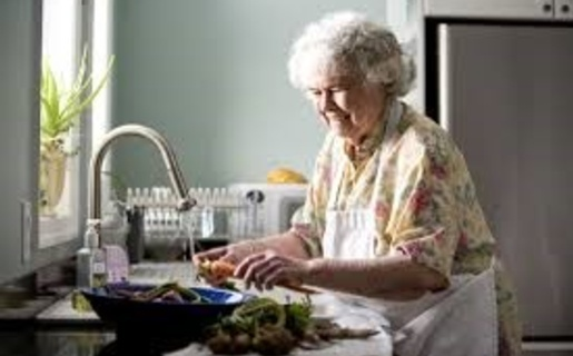 An image of an elderly woman doing the washing up