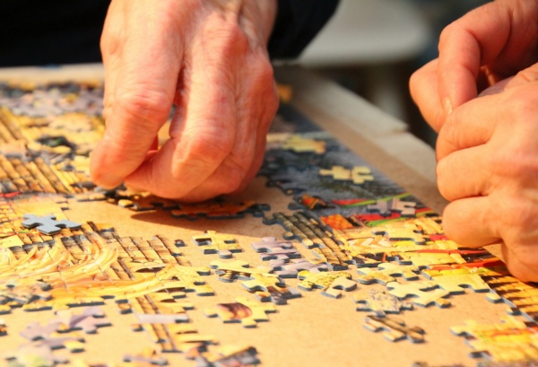 Hands working on a jigsaw puzzle.