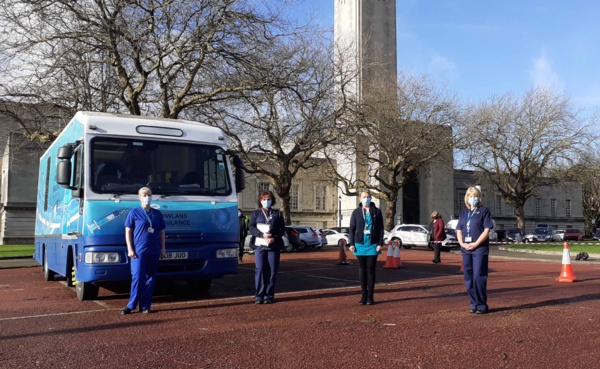 Four nursing staff stand outside the Immbulance parked at Guildhall.