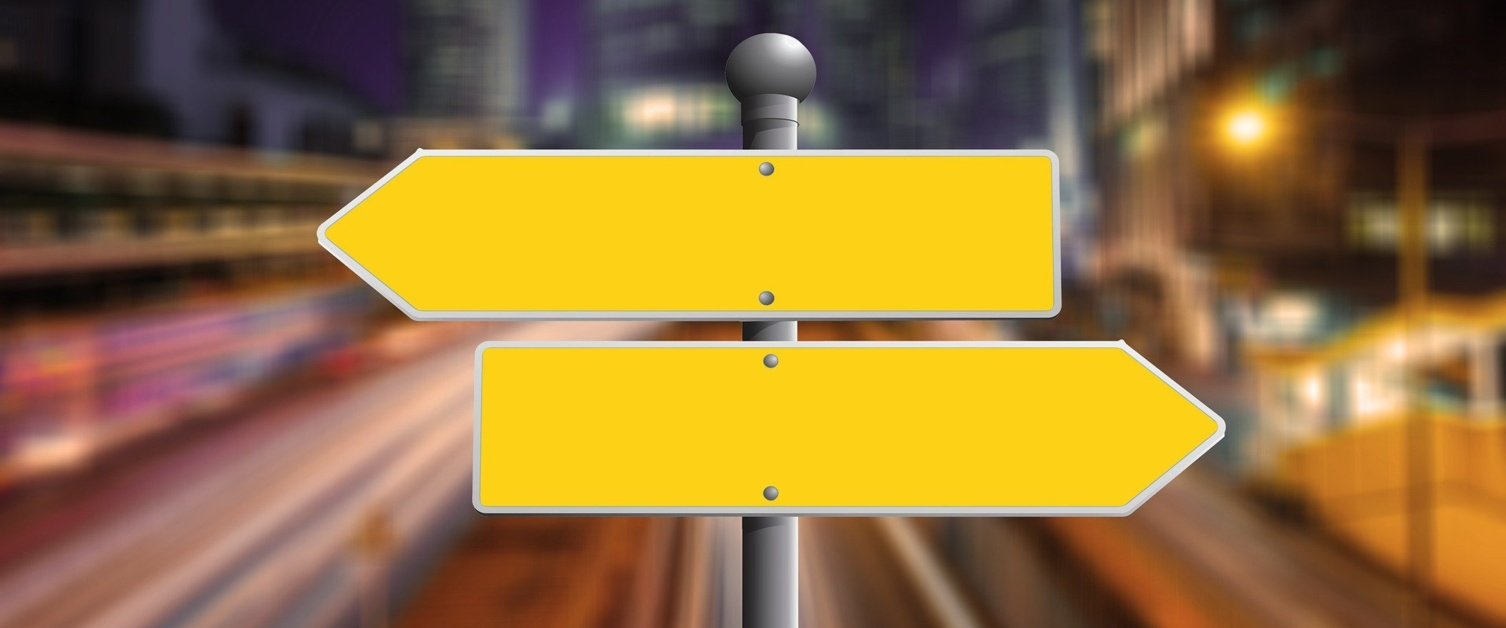 Image shows two blank yellow direction signs pointing in opposite directions.