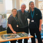 Senior radiographer Tracy Lewis stands with patient Michael Puffett and radiographer Rebecca Lloyd next to the puzzle table.