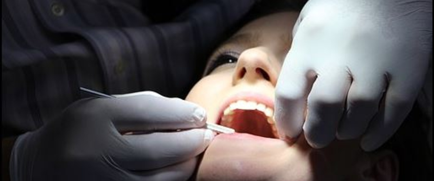 A woman with her mouth open is examined by a dentist.