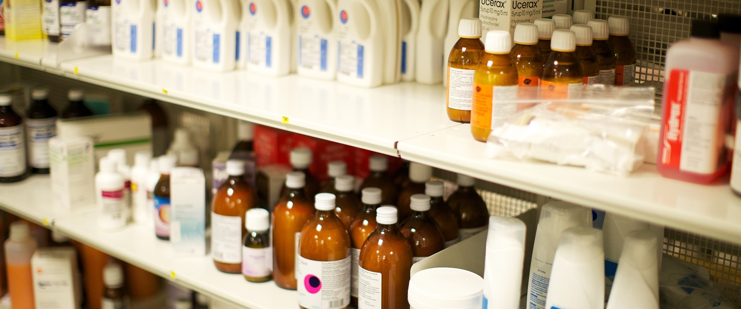 Medicines lined up on a pharmacy shelf.