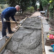 A Ford volunteer lays the concrete for a new accessibility ramp