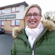 A smiling Anne Robinson standing outside her local GP surgery.