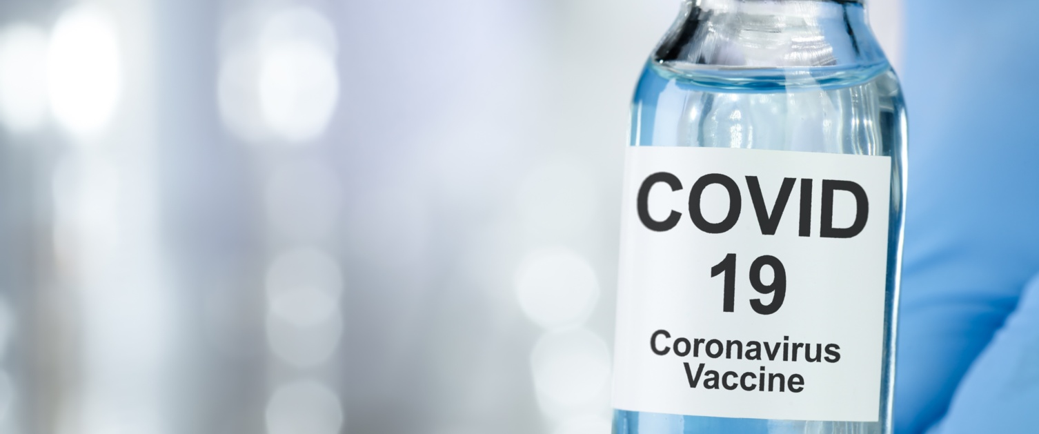Close up of a vial labelled Covid vaccine held between two fingers on a gloved hand.