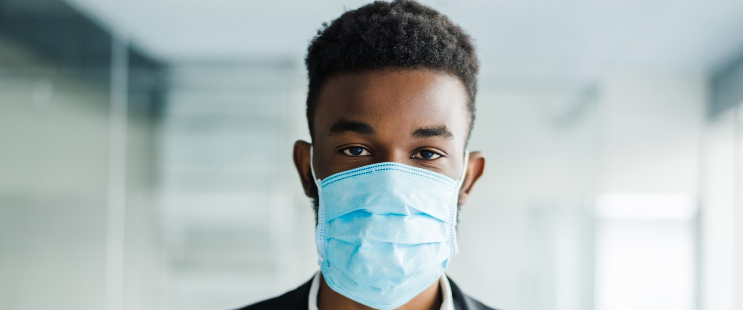 Image shows a young man in a suit facing the camera with a blue surgical mask on.