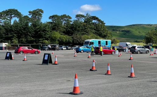 Photo shows a car park with cones set up to mark three lanes. The Immbulance is parked nearby.
