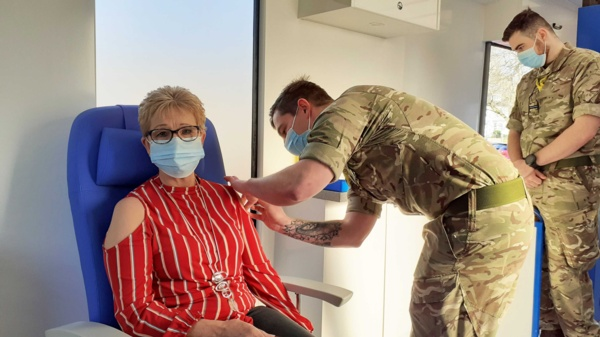 A woman, seated, is vaccinated in the arm by an Army medic.