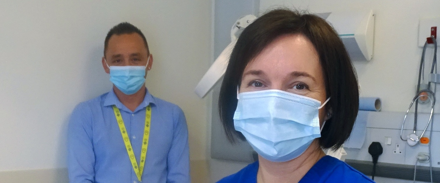 Two people in a hospital examination room
