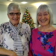 Volunteers Ann Humphrey and Linda Fisher smile in front of a Christmas tree.