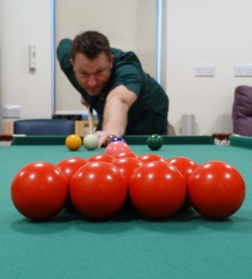 Health care support worker Andrew Ross enjoys a game of pool