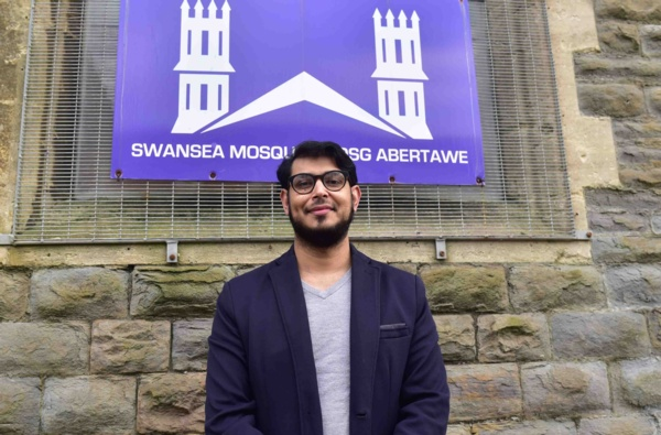 Farid Ali, wearing a navy jacket, stands outside in front of Swansea Mosque sign facing the camera.