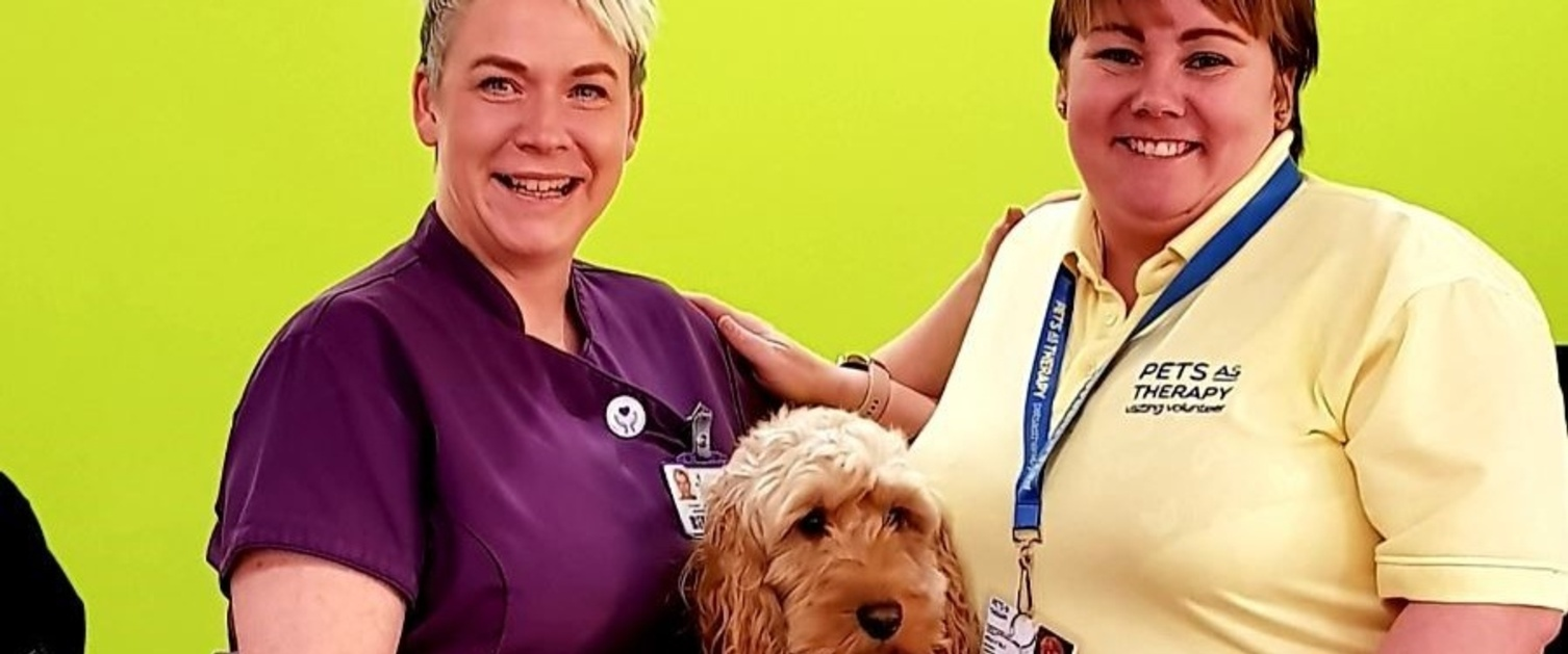 Morriston staff members Nicci Evans and Kelly Elt smiling at reception with dog Jax